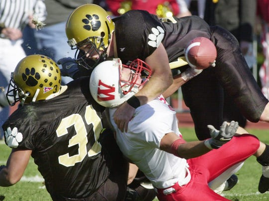 Wabash player Kurt Casper is hit hard by a DePauw defender as he was trying to catch the ball. The ball bounced off and was caught on the 1-yard line by a Wabash teammate. (#31 DePauw is David Blackburn.)