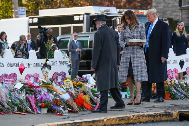 Alongside Tree of Life Synagogue rabbi Jeffrey Myers, President Donald Trump and Melania lay a pebble and a flower on each memorial at the Tree of Life Synagogue in Pittsburgh on Tuesday, Oct. 30, 2018.