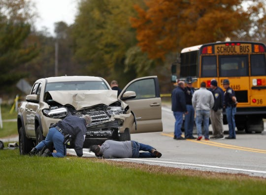 The scene is investigated near 4600 North IN State Rd. 25 north of Rochester, IN, where this pickup truck hit and killed three young children and critically injured a fourth as the children crossed the street to get on this school bus, right, Tuesday, Oct. 30, 2018.  The bus was stopped with lights and stop indicators in use.
