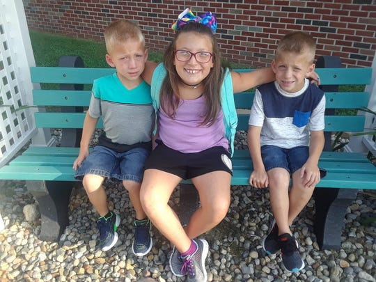 Alivia Stahl, center, sits with her twin brothers, Xzavier and Mason Ingle, in an undated photo provided by the family.