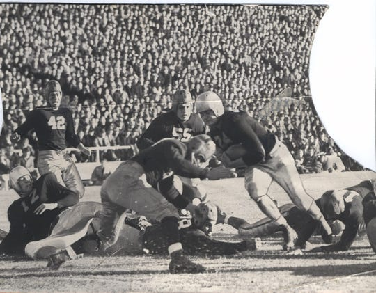 Nile Kinnick is seen running into a tackler during a game in 1939.