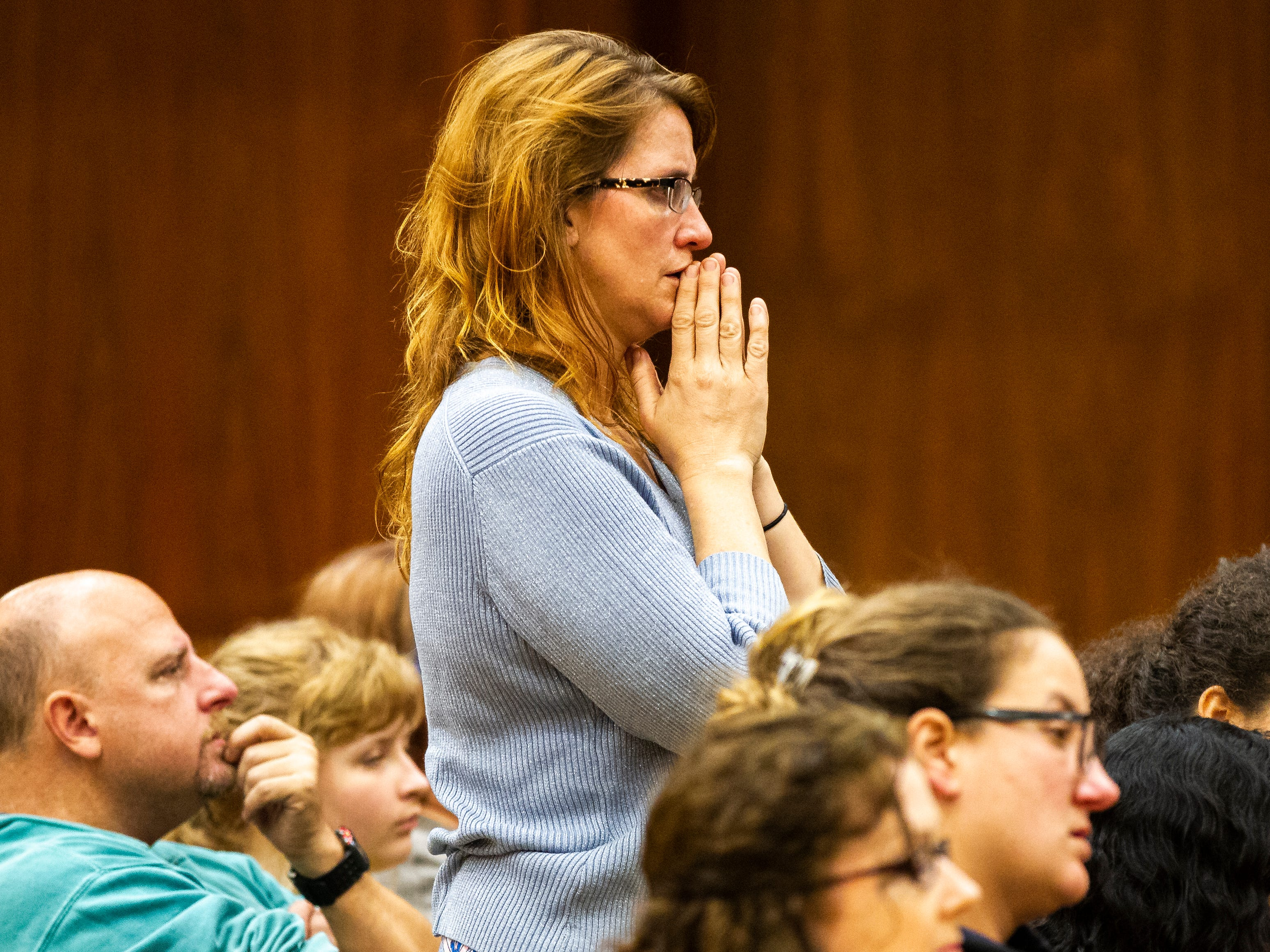 Rachael Hills, of Iowa City prays while community members gather during a vigil on Tuesday, Oct. 30, 2018, in the Iowa Memorial Union second floor ballroom on Tuesday night, Oct. 30, 2018. The vigil was in response to the Pittsburgh synagogue and Louisville shootings.