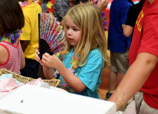 Delaney Blackwood examines a fan at the Multi-cultural Market at Community Montessori, Wednesday, October 31.