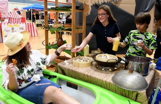 Lydia Pratt shares sticky rice to Dr. Callie Dollar during the multi-cultural market at Community Montessori, Wednesday, October 31.