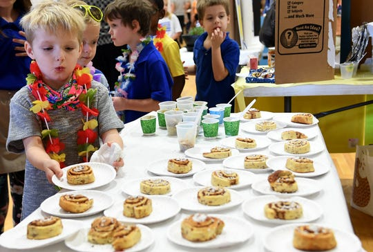 Tanner Avera grabs a cinnamon roll off the table during the multi-cultural market at Community Montessori, Wednesday, October 31.