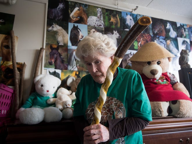 Jill McKenzie, 74, stands in front of stuffed animals, which she used to provide to children through a charity she founded. Now legally blind, she carves spiral walking sticks from sumac branches in her modest apartment home.