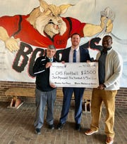 Charlie Pratt of Modern Woodmen Fraternal Financial, pictured middle, presents a check to Central High's Athletic Director J.D. Lambert and Head Coach, Bryson Rosser in the spring of 2018.