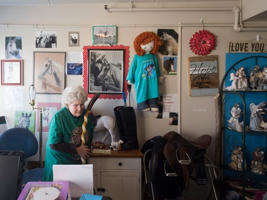 Photographs or horses and line the walls of Jill McKenzie's modest apartment home. McKenzie is a former Arabian horse trainer and philanthropist who provided stuffed toys to children. She is a legally blind but her most recent passion is carving spiral walking sticks.