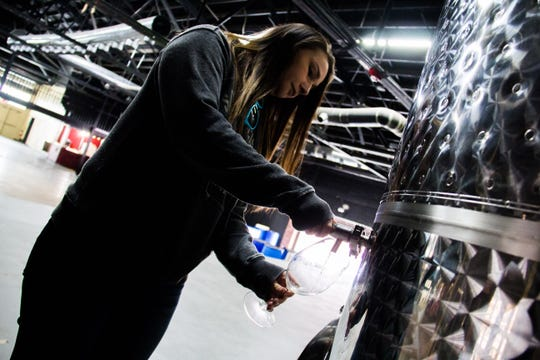 Katie Galyon, owner of the Winery at The International, pours a glass of wine from a tank on Oct. 31, 2018.