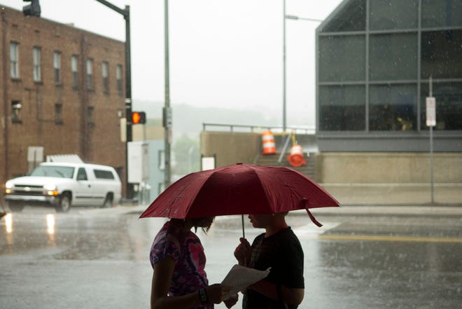 Brooke Buckner, 11, left, and Miles Foster, 9, share an umbrella in the rain while waiting outside the Bijou Theatre on Wednesday, July 18, 2012. The two were waiting to be picked up after attending a summer acting camp at the Theatre.