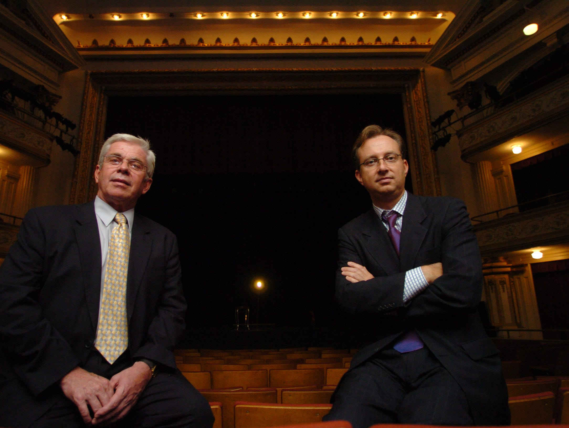 """Bijou Theatre board president Chuck Morris (right) and consultant Bill Mitchell inside the theatre where a """"ghost light"""" is left on stage in 2004"""