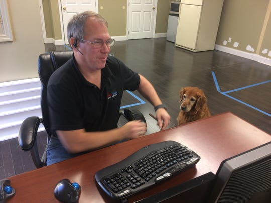 Staff members Glen Stafford and Lollipop attend to a day's work behind the computer.