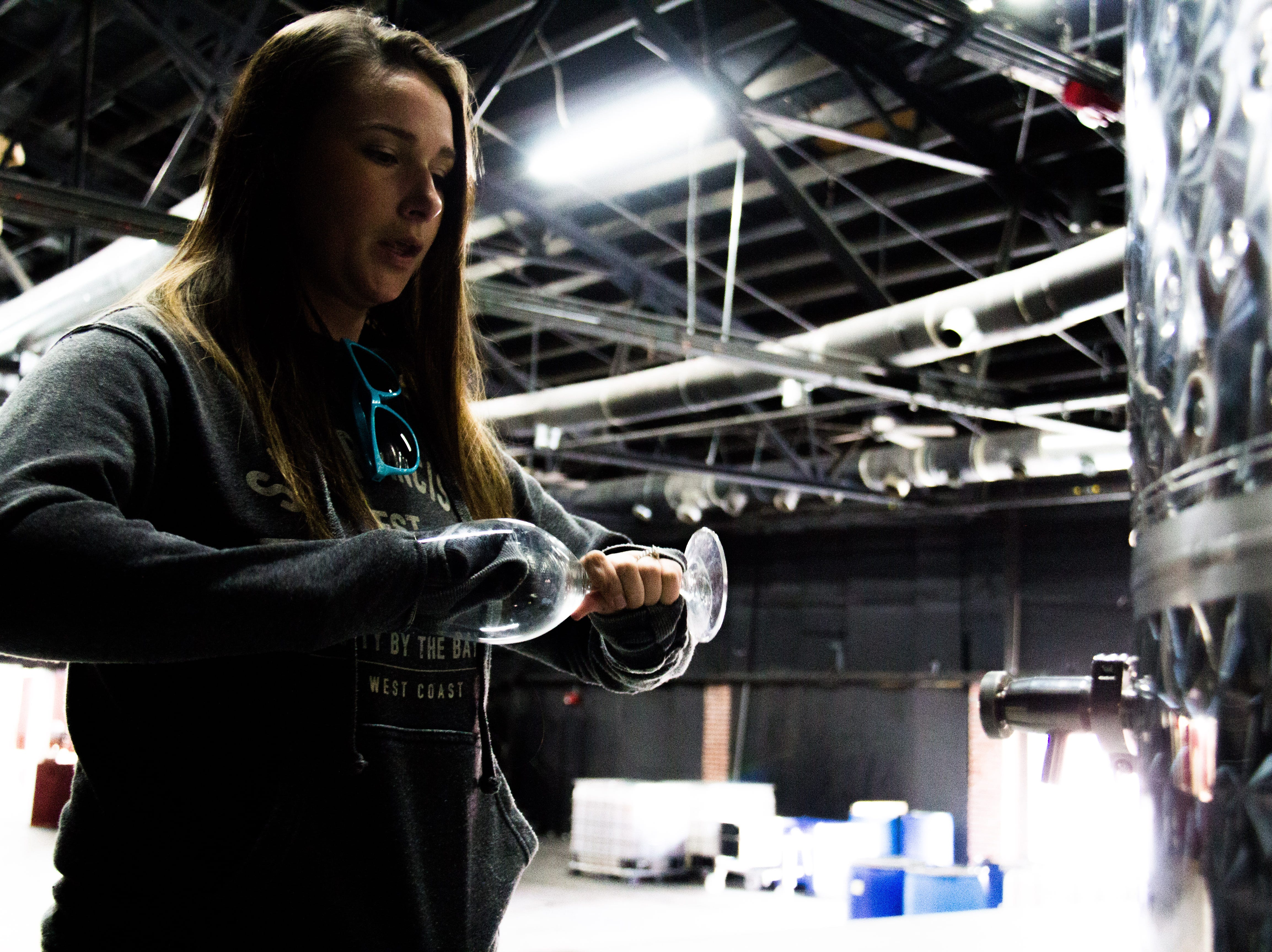 Katie Galyon, owner of the Winery at The International, prepares to pour a glass of wine from a tank on Oct. 31, 2018.