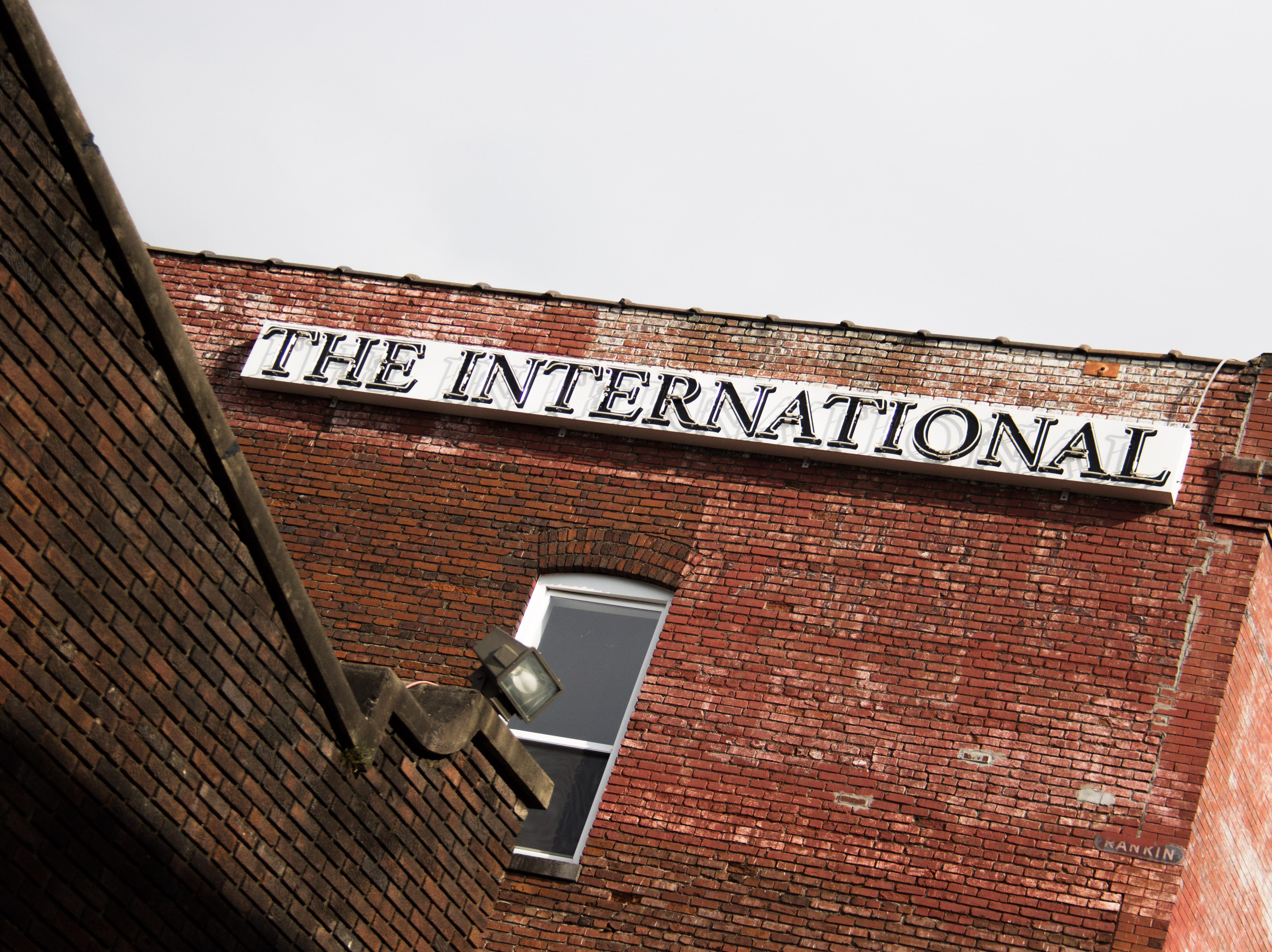 A sign for The International hangs on the side of The Concourse music venue, one of three buildings on the property.