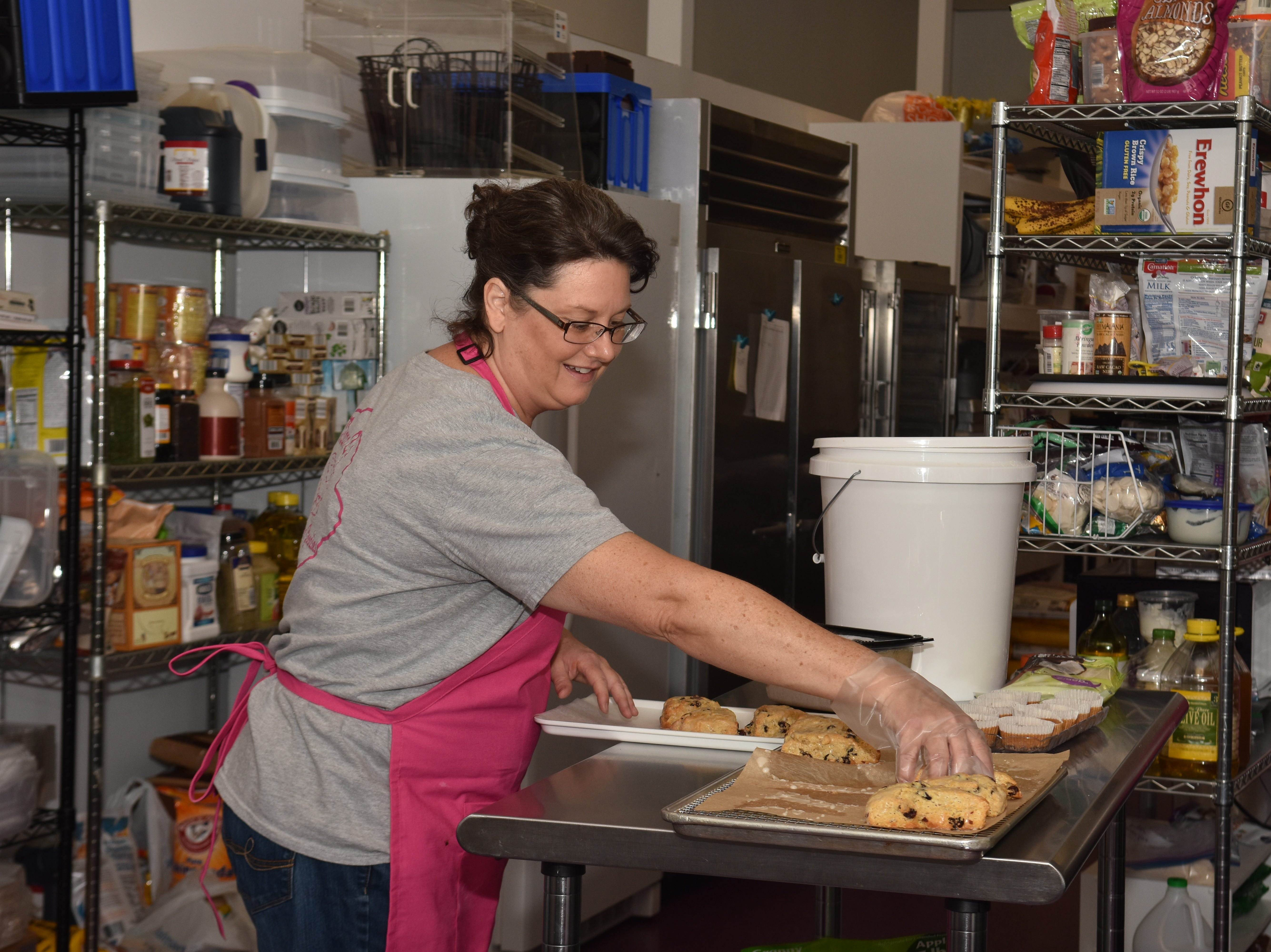 """Lynnette Casazza, """"Mama C"""", puts fresh cranberry scones on a tray for the bakery case."""