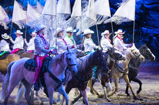 Performers from Dolly Parton's Stampede dinner attraction ride horses during the holiday show.