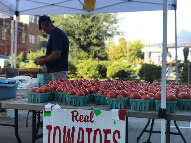 Eric Morrow sets up his tomato stand at the Red Stick Farmers Market early on a recent Saturday in Baton Rouge.