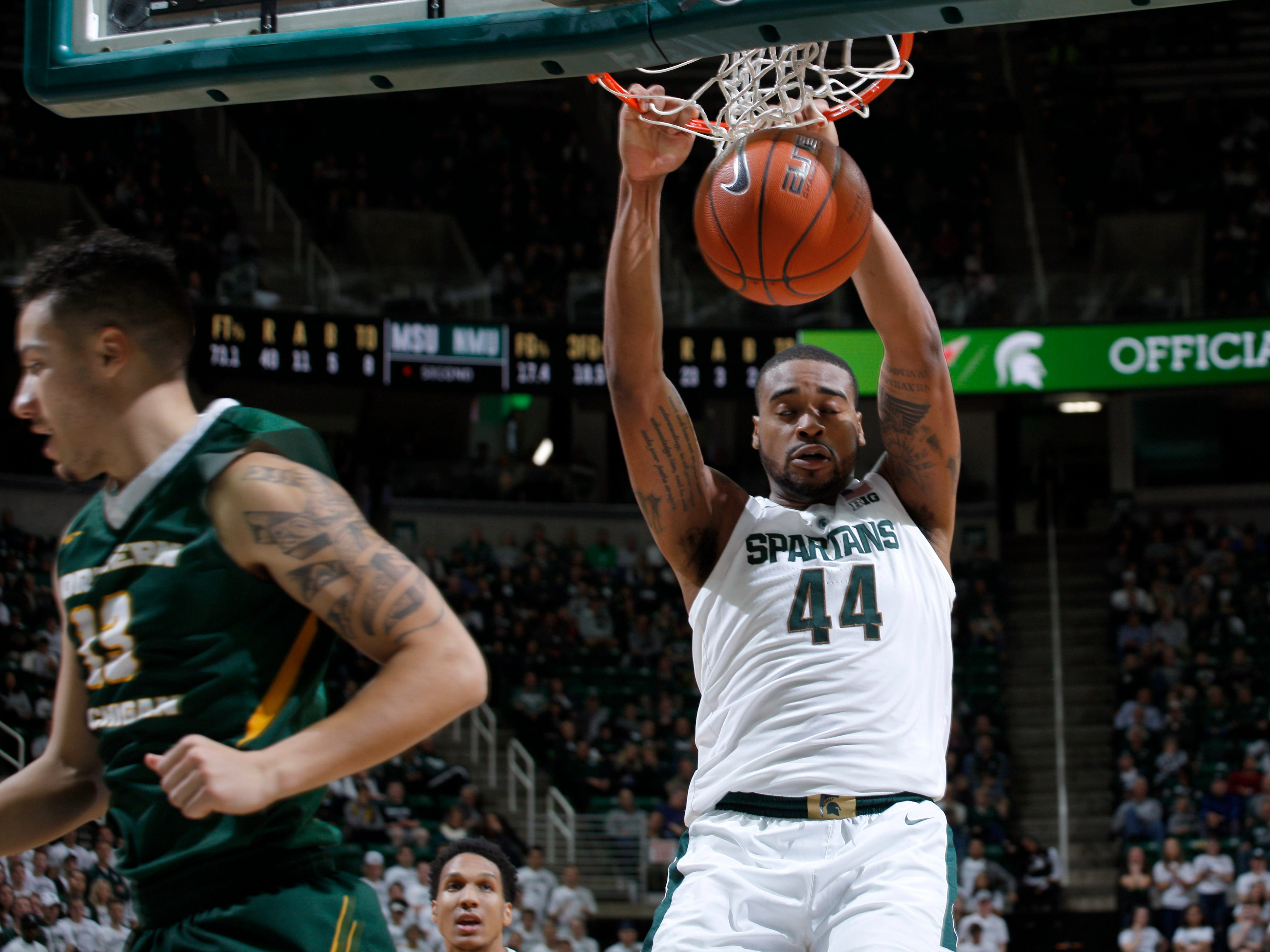 Michigan State's Nick Ward (44) dunks against Northern Michigan's Myles Howard, Tuesday, Oct. 30, 2018, in East Lansing, Mich.