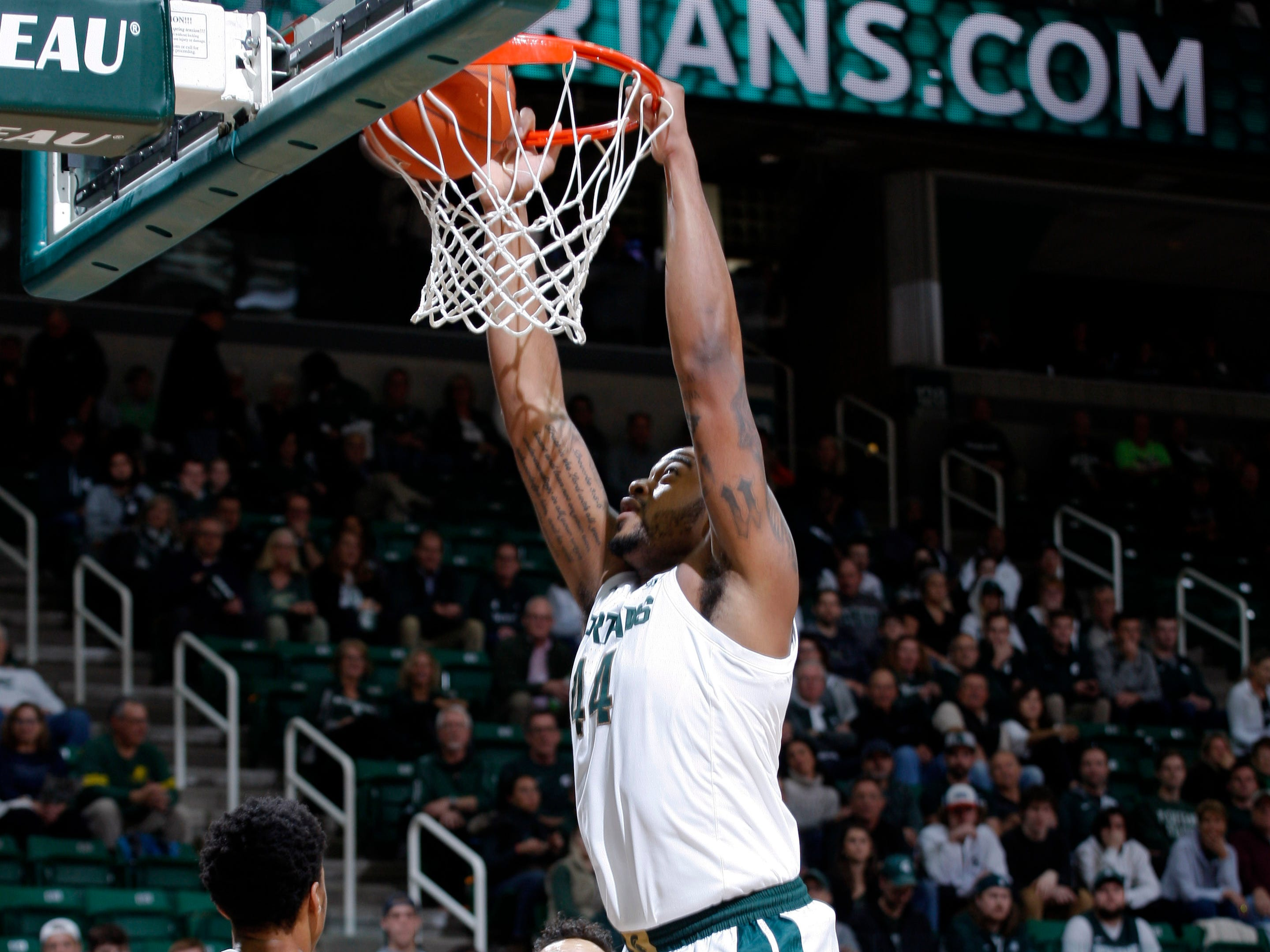 Michigan State's Nick Ward dunks over Northern Michigan's Myles Howard (33) and Isaiah Johnson (13), Tuesday, Oct. 30, 2018, in East Lansing, Mich.