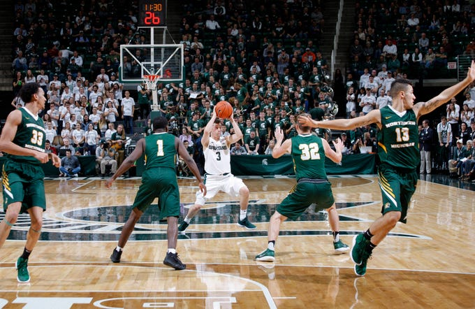 Michigan State's Foster Loyer (3) looks to pass against Northern Michigan's Myles Howard (33), Naba Echols (1), Marcus Matelski (32) and Isaiah Johnson (13), Tuesday, Oct. 30, 2018, in East Lansing, Mich.