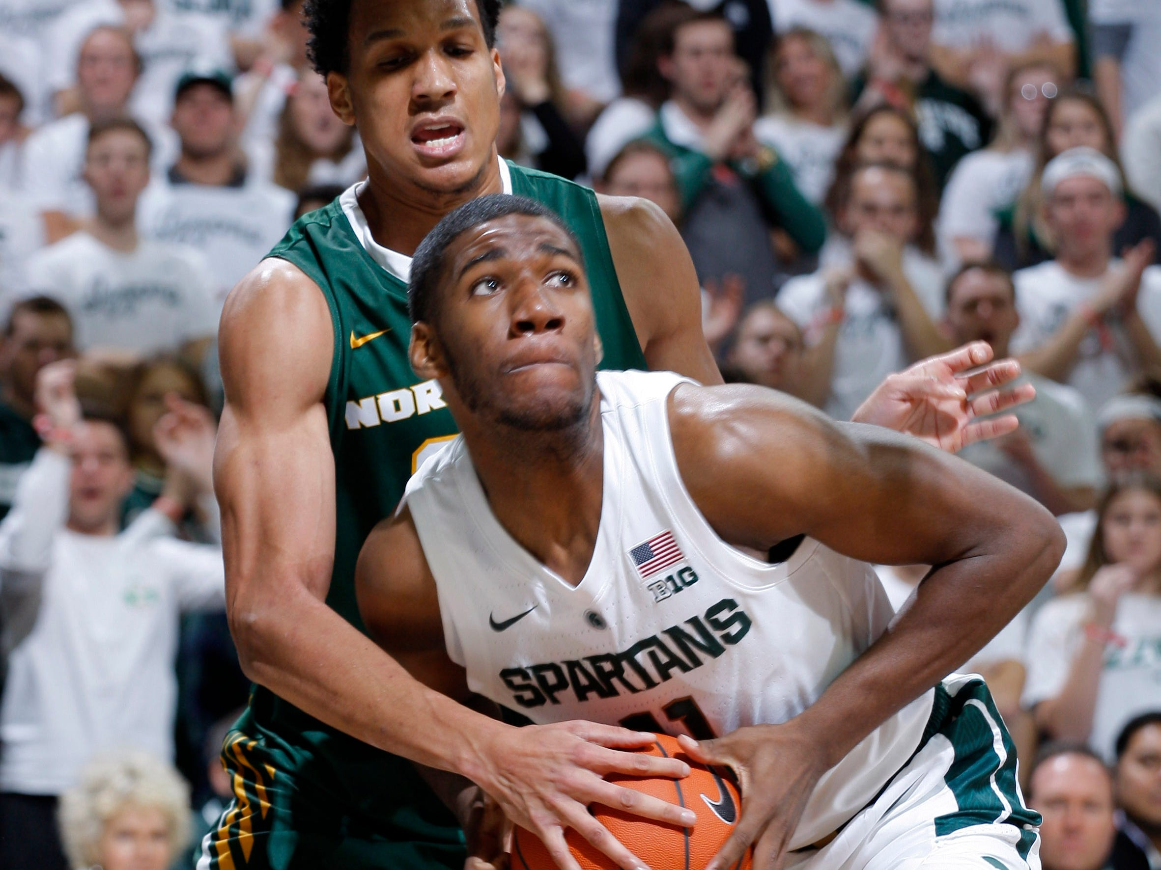 Michigan State's Aaron Henry, front, and Northern Michigan's Myles Howard, rear, vie for the ball, Tuesday, Oct. 30, 2018, in East Lansing, Mich.
