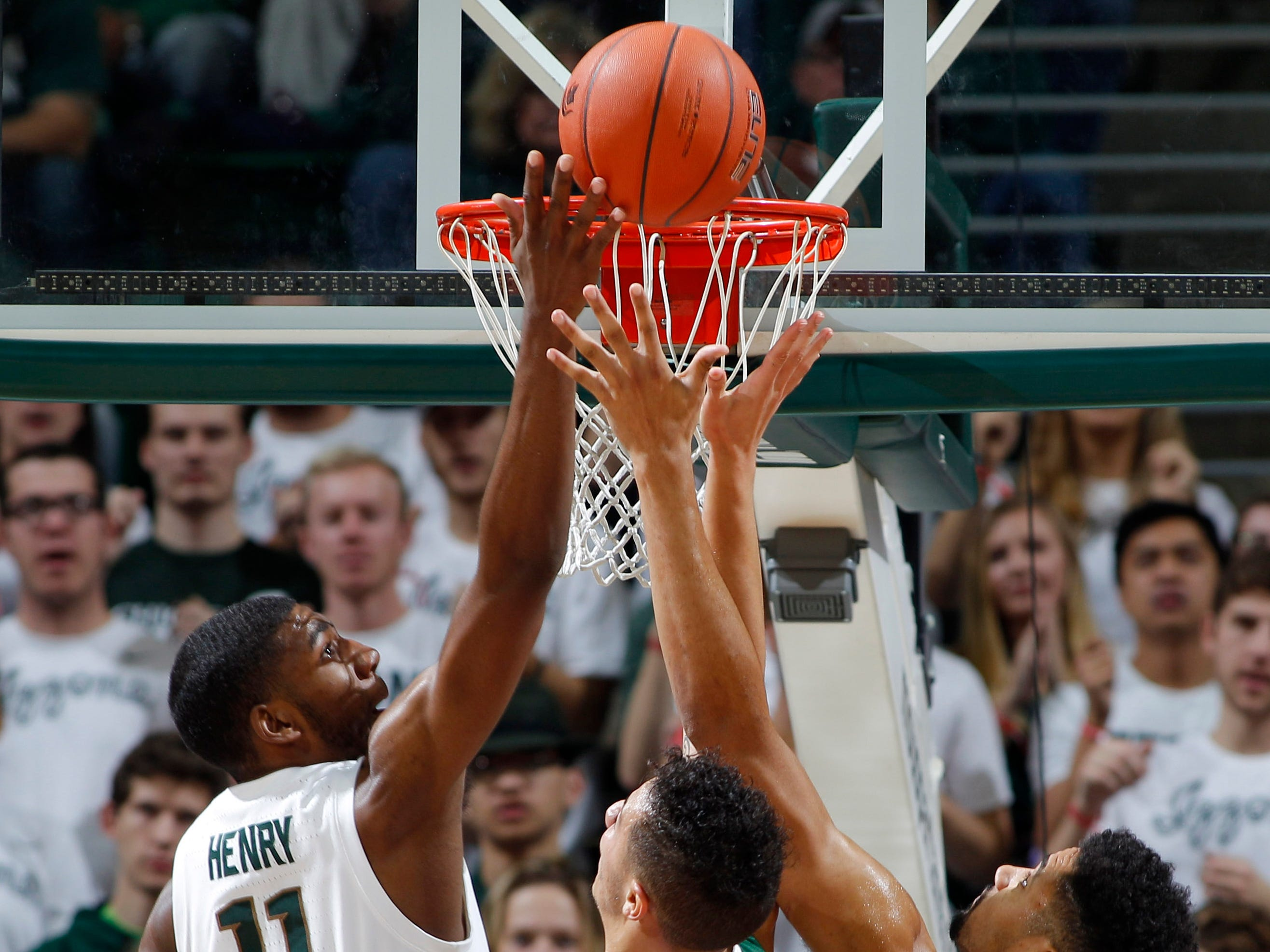 Michigan State's Aaron Henry (11) and Kenny Goins (25) and Northern Michigan's Isaiah Johnson, center, reach for a rebound, Tuesday, Oct. 30, 2018, in East Lansing, Mich.
