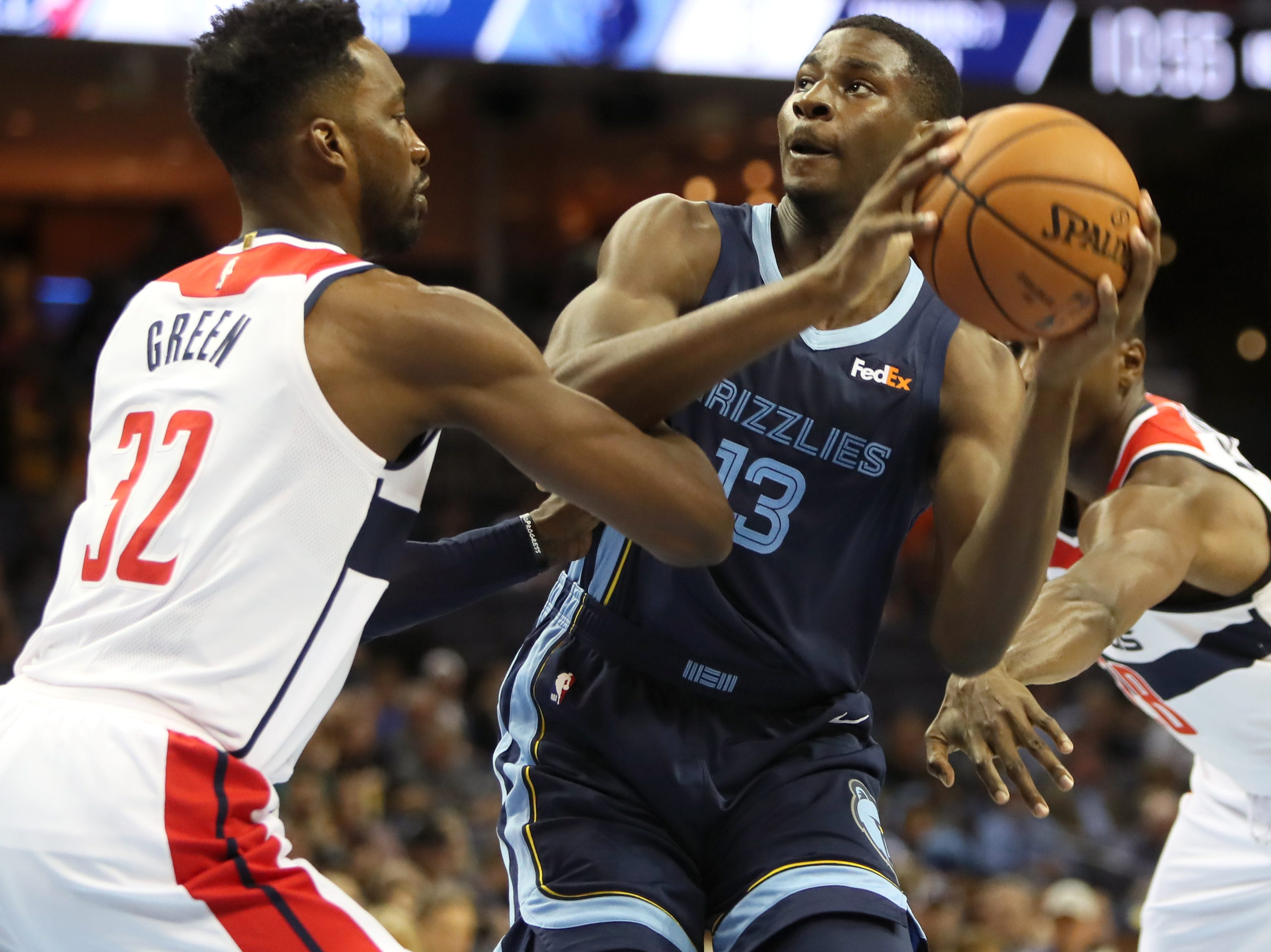 Memphis Grizzlies forward Jaren Jackson Jr. battles against Washington Wizards forward Jeff Green, left and Ian Mahinmi to get a shot up during their game at the FedExForum on Tuesday, Oct 30, 2018.