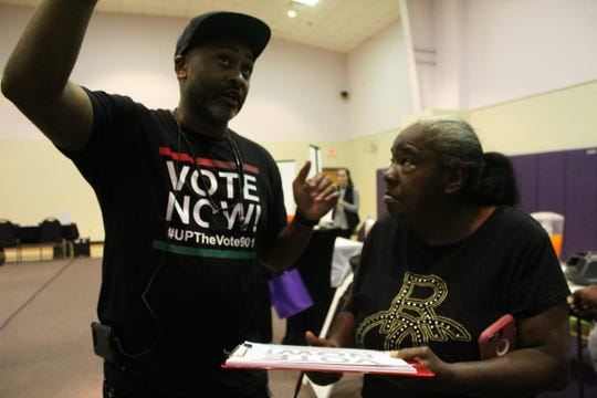 Pastor Earle J. Fisher talks with a Memphis resident about where to cast a ballot.