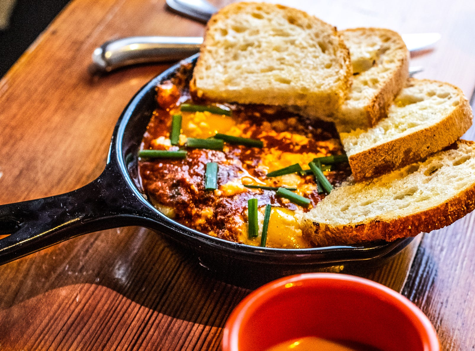 The Shakshuka Skillet is made with two sunny side up eggs in finger hot pepper-tomato sauce, organic arugula, garlic spinach, feta and Yukon gold potatoes and is served with toasted sourdough.