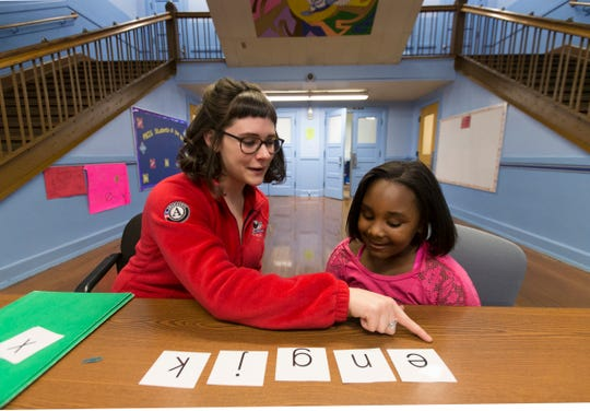 Americorps worker Mikayla Kinnion (left) works with first grade student Je'Nay Williams on sounding out consonants at Forest Home Avenue School in Milwaukee in 2016.