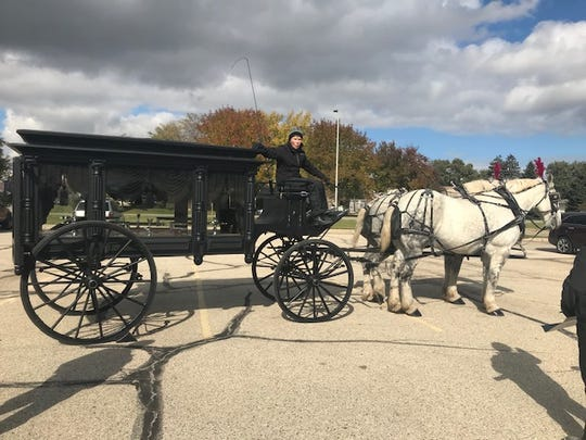 Mary Jane Swedberg of Hoof Beats Express in Oconomowoc waits in Zablocki Park on Oct. 16 to carry a casket in a horse-drawn hearse.