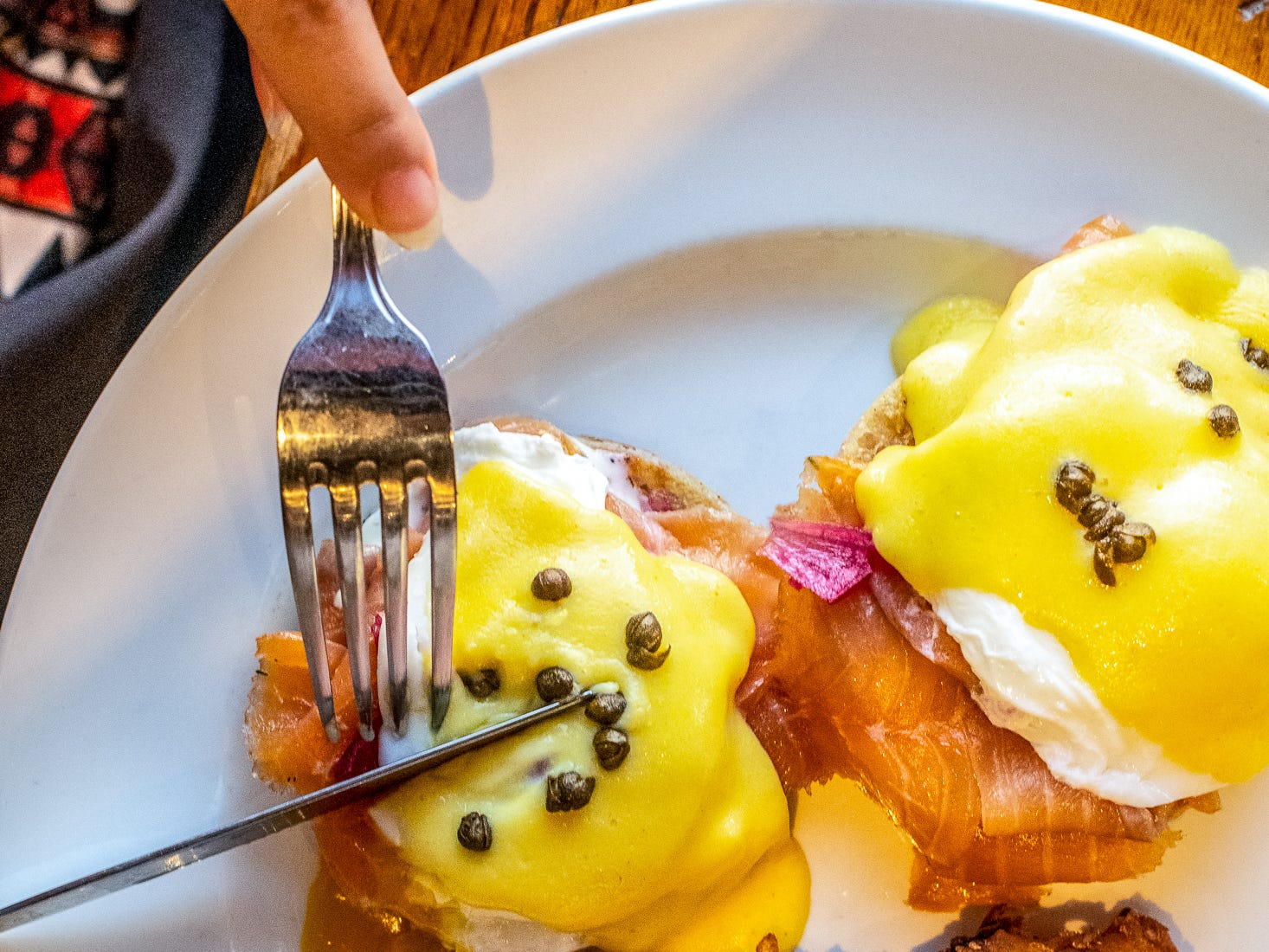 The new Royale Benedict is topped with smoked salmon, dill crème fraîche, pickled pearl onions, poached eggs, house hollandaise and fried capers.