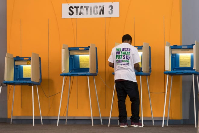 A man marks a ballot during early voting in Milwaukee.