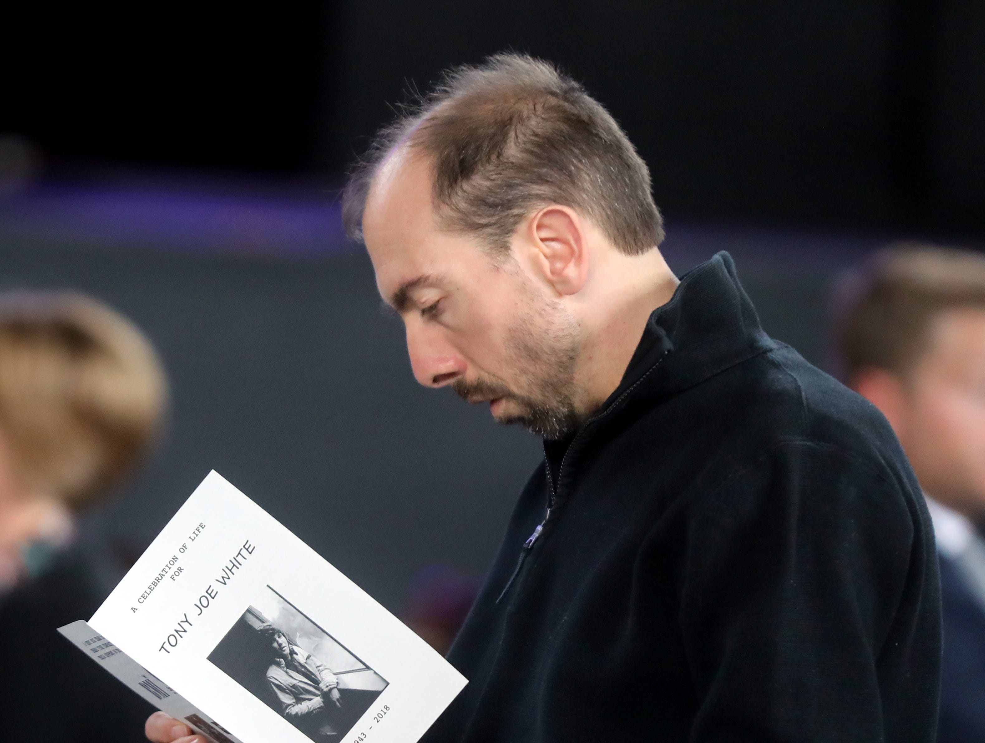 Nathan Collie reads the program during a Celebration of Life service held for singer-songwriter Tony Joe White at Marathon Music Works Wednesday, October 31, 2018.