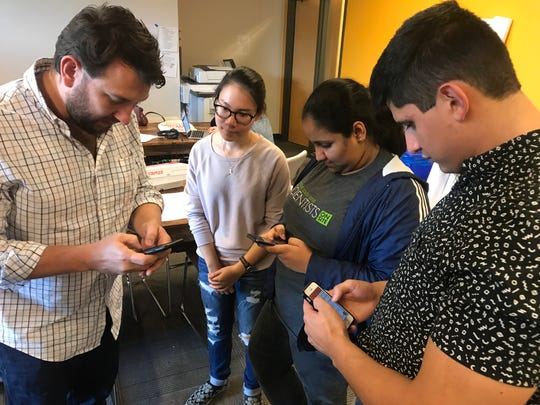 Brandon Puttbrese of TIRRC Votes shows young canvassers Vy Le, 18, Nethmi Hewavithana, 17 and Jorge Salles Diaz, 22, how to use a mobile canvassing out before they head out to knock on doors and talk to community members about voting in the 2018 midterm election. TIRRC Votes will be holding a forum Monday for candidates in the upcoming mayoral and Metro Council election.