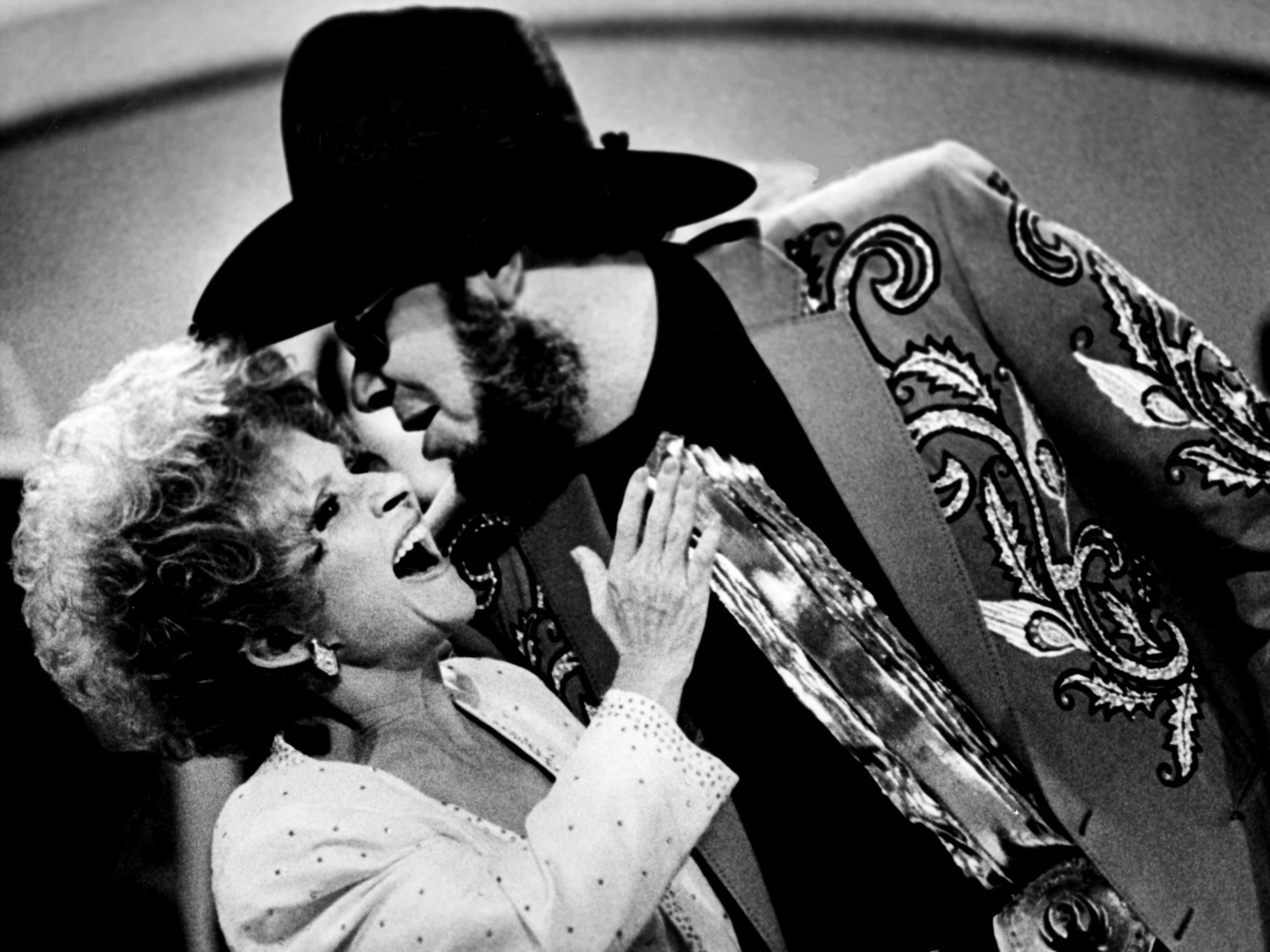 Hank Williams Jr. celebrates his second straight triumph as the Entertainer of the Year by sweeping pop-country queen Brenda Lee off her feet during the CMA Awards show at the Grand Ole Opry on Oct. 10, 1988. Williams also won the Album of the Year award.