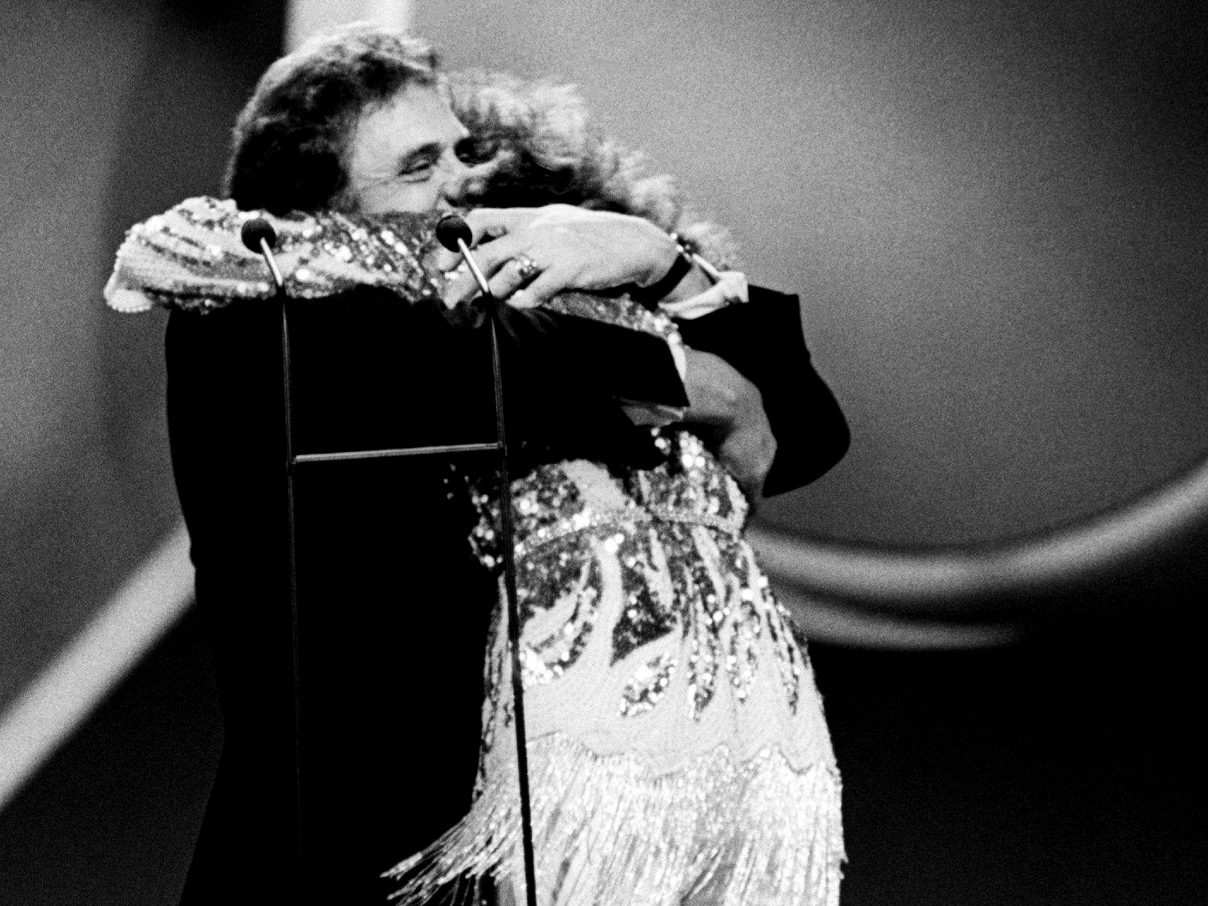 Country music legend Johnny Cash welcomes Loretta Lynn into the Country Music Hall of Fame during the 22nd annual CMA Awards gala at the Grand Ole Opry House on Oct. 10, 1988.