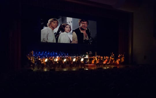 """A symphony performs """"Star Wars"""" music similar to how it would have looked on Oct. 30, 2018, at Artis—Naples.  Presentation licensed by Disney Concerts in association with 20th Century Fox, Lucasfilm Ltd., and Warner /Chappell Music. © 2017 & TM LUCASFILM LTD. ALL RIGHTS RESERVED"""