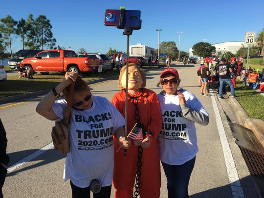 A Donald Trump supporter poses while wearing a Hillary Clinton mask and prison garb, hours before the President was expected for a 7 p.m. rally at Hertz Arena in Estero on Wednesday, Oct. 31, 2018.