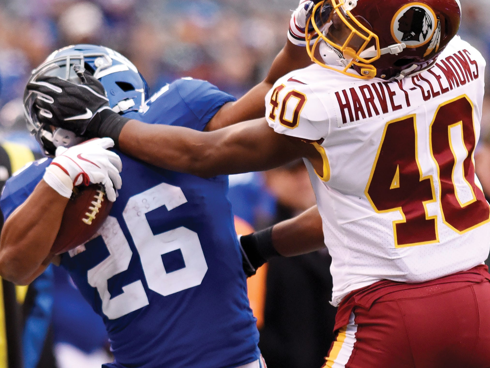 New York Giants running back Saquon Barkley (26) and Washington Redskins linebacker Josh Harvey-Clemons (40) stiff-arm each other in the second half. The Giants lose to the Redskins 20-13 on Sunday, Oct. 28, 2018, in East Rutherford. (Danielle Parhizkaran/@danielleparhiz)