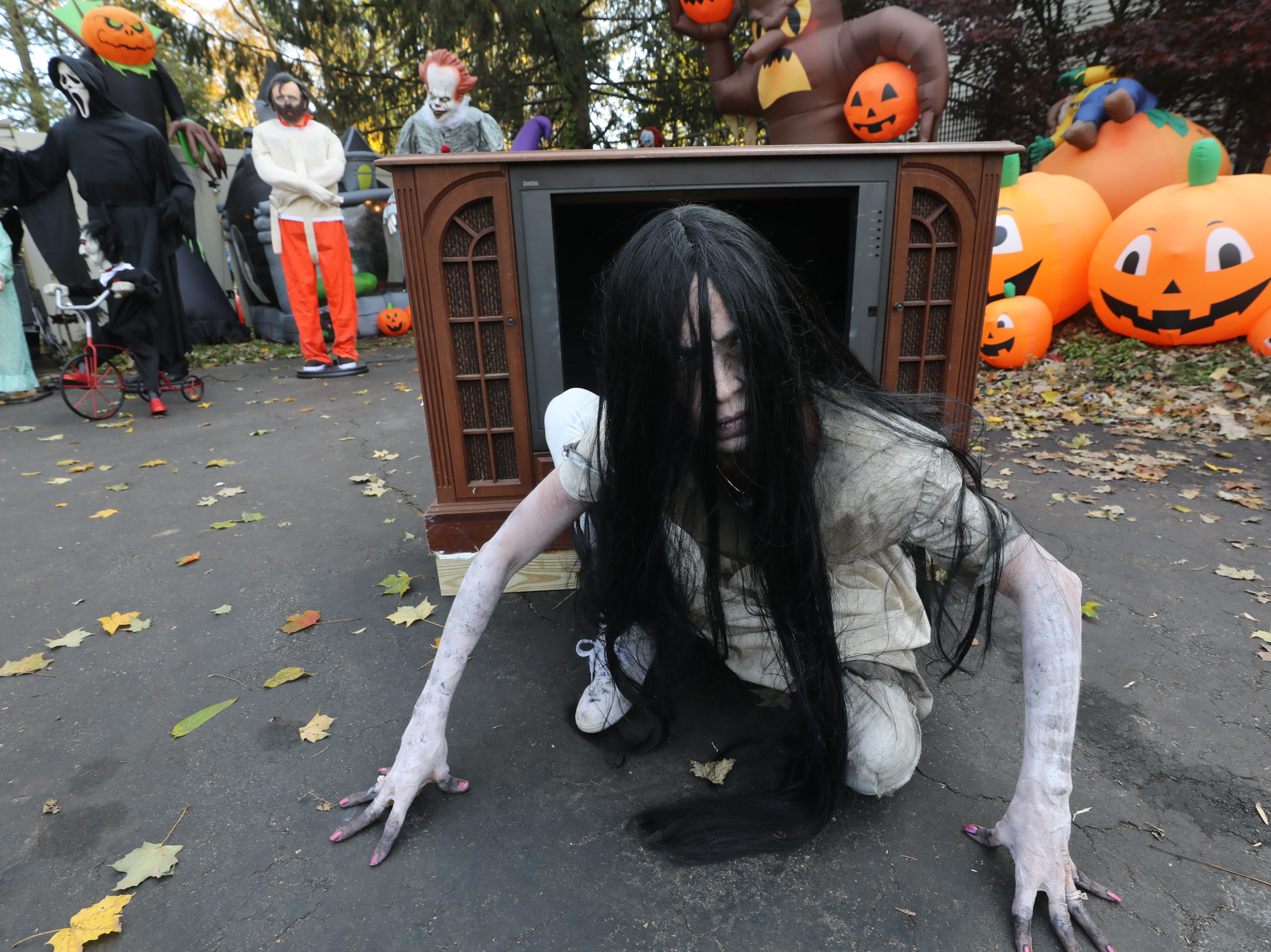 Marisol Cole of Wayne is dressed as the little girl from The Ring as she prepares to climb out of this television set. Gina and Rich Martorano start to put this huge Halloween display, on Fairfield Rd., together in August and will be dismantling it tomorrow to make room for their Christmas display. Parents and kids from the area came to see and be scared.