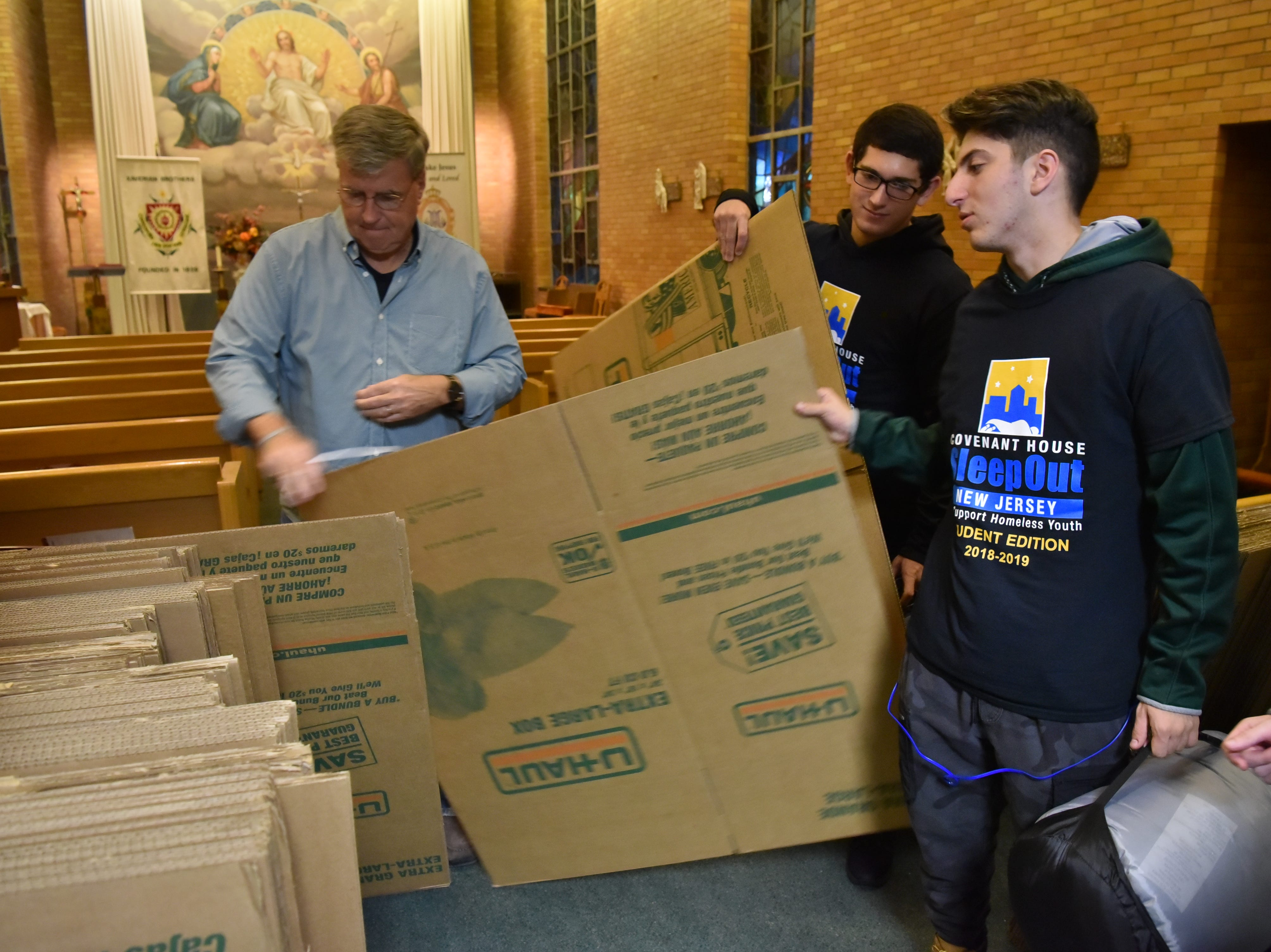 Students receive cardboard boxes in which they will spend the night outside. Members of the St. Joe's student body and faculty raise money for the North Jersey chapter of Covenant House by spending the night out.
