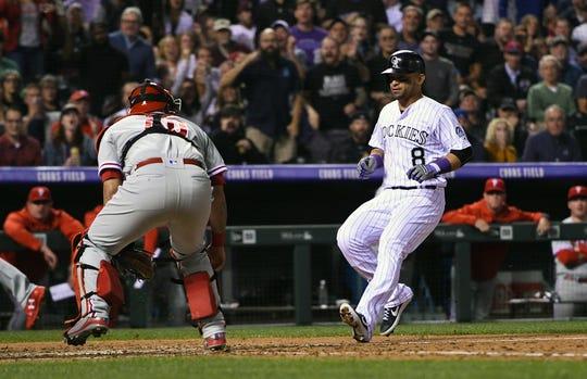 Sep 24, 2018; Denver, CO, USA; Colorado Rockies left fielder Gerardo Parra (8) scores past Philadelphia Phillies catcher Wilson Ramos (40) on a throwing error in the sixth inning at Coors Field.