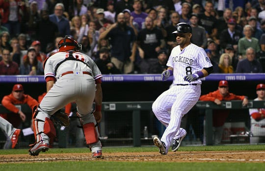 Sep 24, 2018; Denver, CO, USA; Colorado Rockies left fielder Gerardo Parra (8) scores past Philadelphia Phillies catcher Wilson Ramos (40) on a throwing error in the sixth inning at Coors Field.