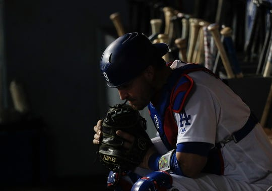 Los Angeles Dodgers catcher Yasmani Grandal sits in dugout during the eighth inning in Game 5 of the World Series baseball game against the Boston Red Sox on Sunday, Oct. 28, 2018, in Los Angeles.
