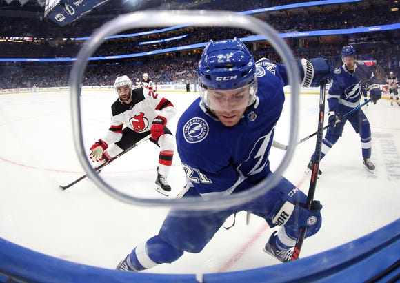 Oct 30, 2018; Tampa, FL, USA; Tampa Bay Lightning center Brayden Point (21) skates with the puck by the boards as New Jersey Devils right wing Kyle Palmieri (21) defends during the first period at Amalie Arena.