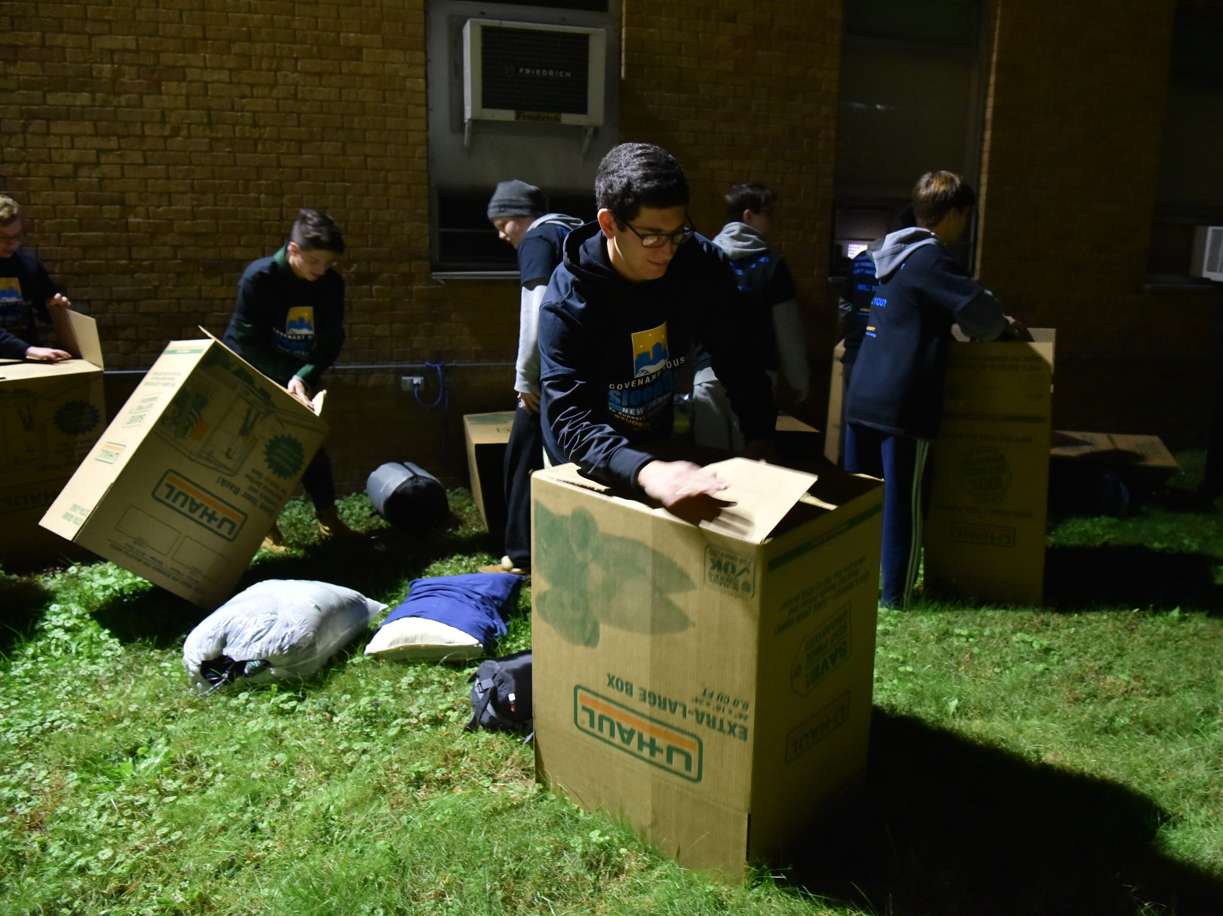 Students participating in the Covenant Sleepout, prepare their cardboard boxes for spending the night out.