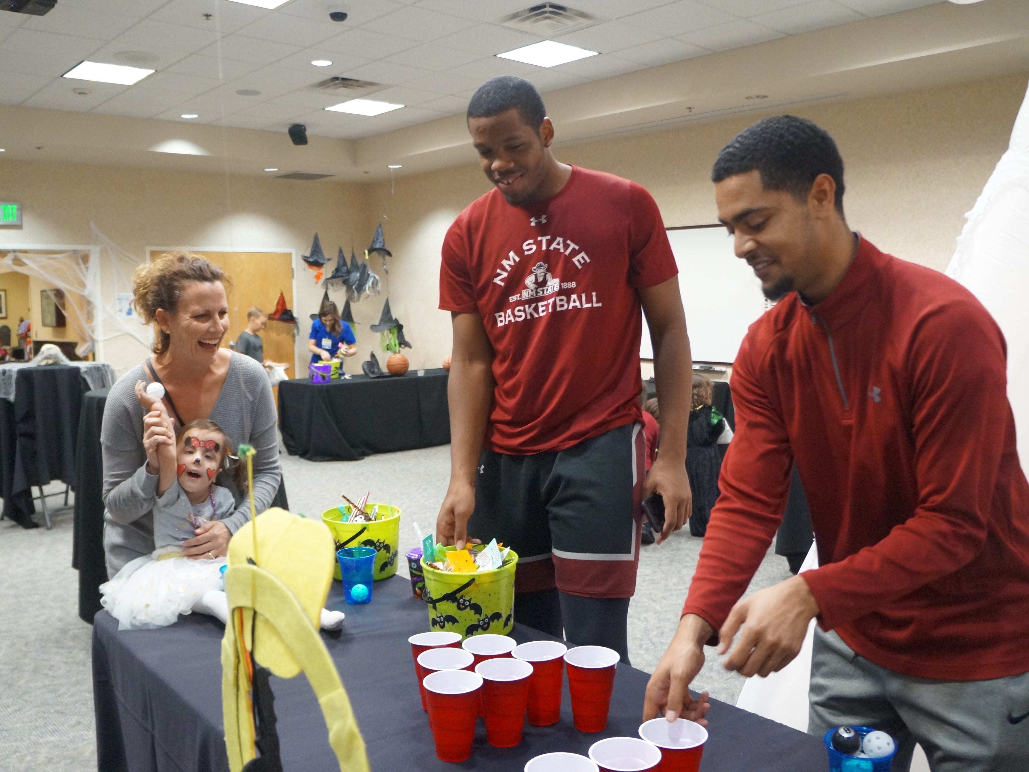Members of the New Mexico State basketball program help out at the  Memorial Medical Center NICU Reunion Carnival. The hospital was host to a reunion of children who had been helped by the hospital's neonatal intensive care unit. Children came dressed in costume for the second NICU Reunion Carnival, held Tuesday, Oct. 30. The children, parents and hospital staff enjoyed food and games for the afternoon.
