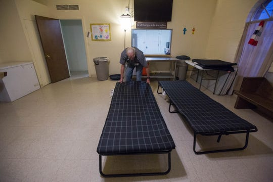 Bobbie Hutson, a volunteer at El Calvario United Methodist Church, sets up cots for the 23 newly arrived asylum seekers, Tuesday October 30, 2018.