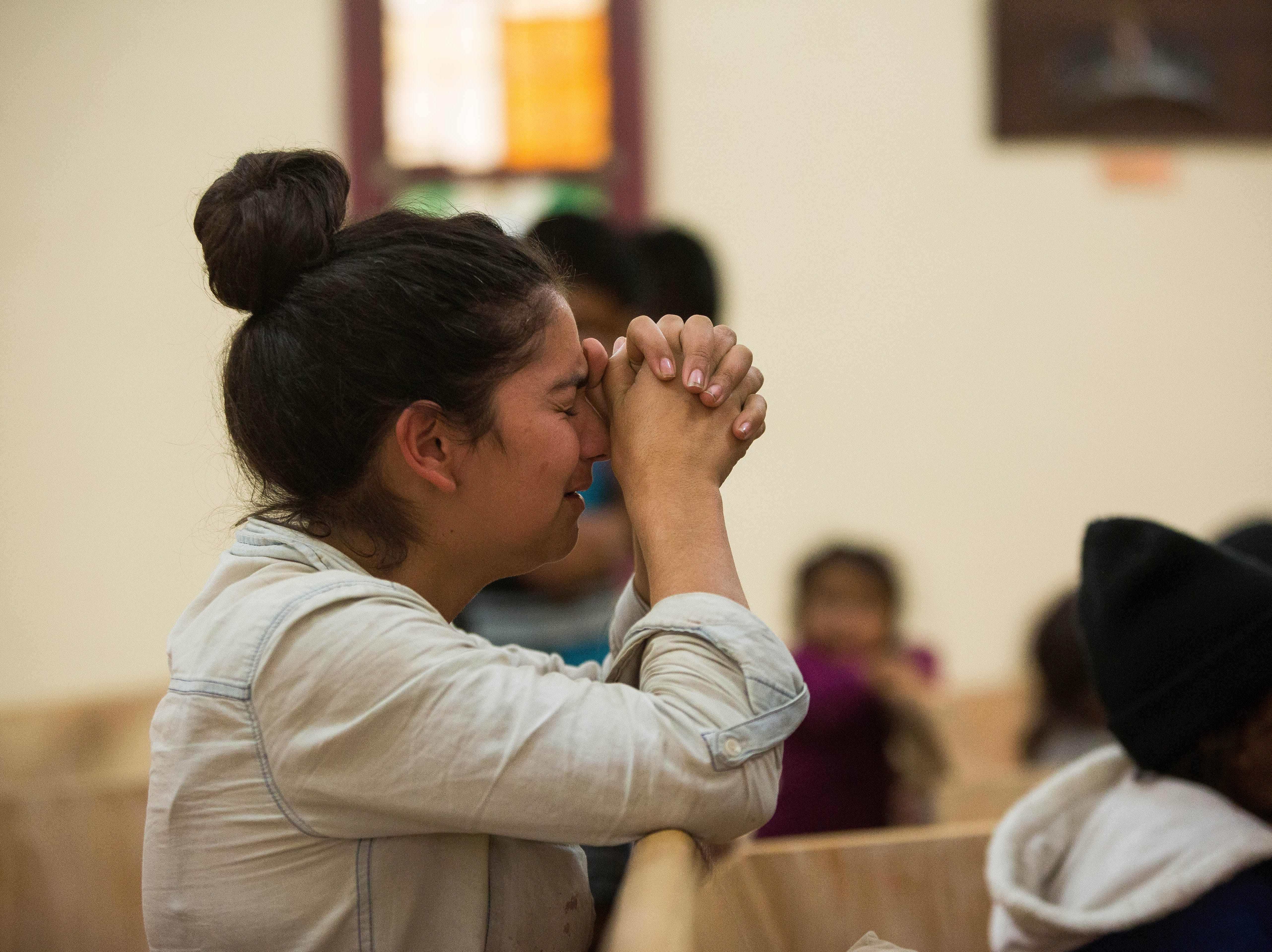 Riccy, an immigrant seeking asylum from Honduras joins the 22 other immigrants in a prayer lead by Pastor George Miller and Jorge Renteria at El Calvario United Methodist Church, Tuesday, October 30, 2018.